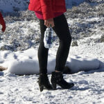a girl hiking in the snow with high heeled boots