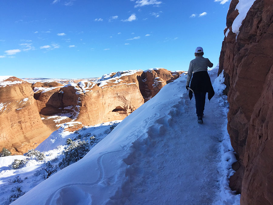 Hiking on ice with boot spikes - crampons - in Utah at Arches National Park.